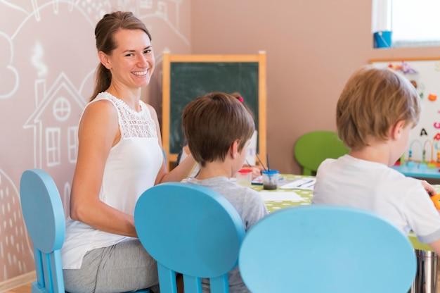 Professora feliz assistindo crianças