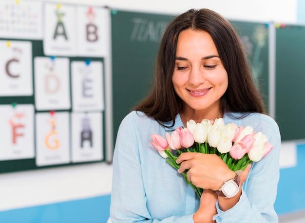 Professora feliz com o buquê de flores que recebeu