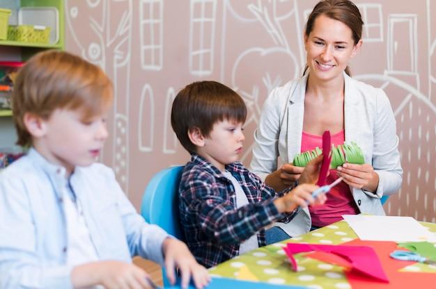 Professora feliz cortando papel com crianças