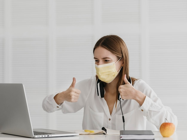 Professora frequentando seu curso online e usando máscara médica