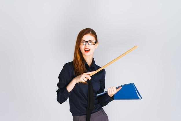 Professora jovem apontando uma régua para algum lugar segurando uma pasta azul com documentos, sorrindo, olhando para a câmera