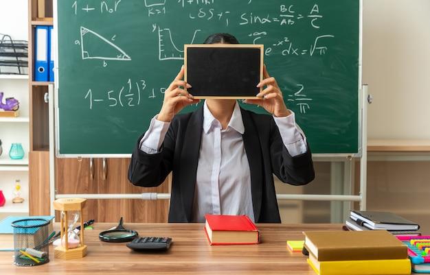 Professora jovem se senta à mesa com as ferramentas da escola cobrindo o rosto com uma lousa pequena