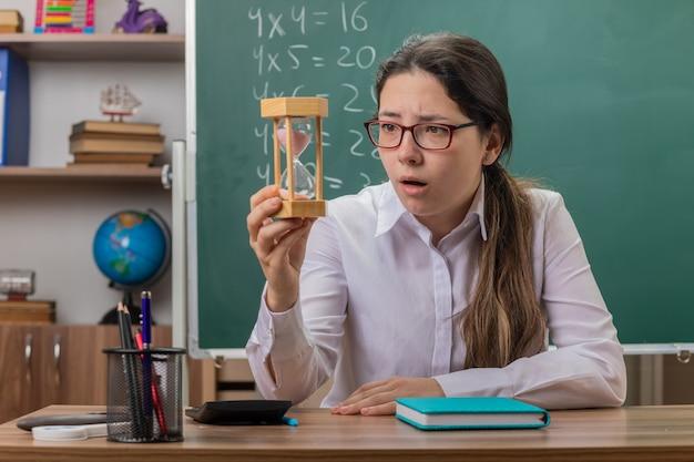 Professora jovem usando óculos com ampulheta olhando para ela surpresa se preparando para a aula sentada na mesa da escola em frente ao quadro-negro na sala de aula