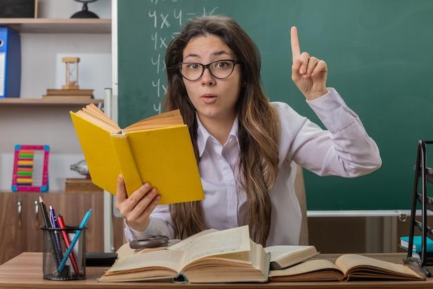Professora jovem usando óculos e lendo livros, parecendo surpresa, mostrando o dedo indicador sentado na carteira da escola em frente ao quadro-negro na sala de aula