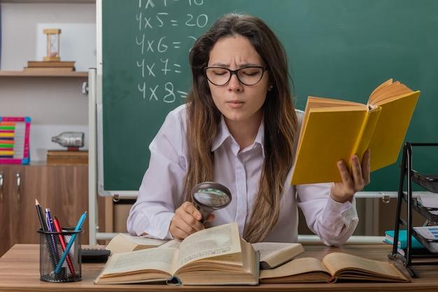 Professora jovem usando óculos, olhando para um livro através de uma lupa, ficando intrigada sentada na mesa da escola em frente ao quadro-negro na sala de aula