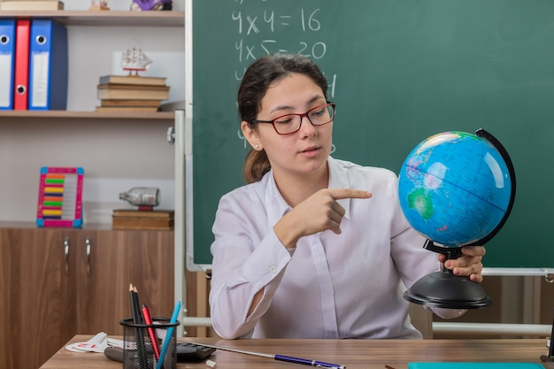 Professora jovem usando óculos segurando um globo explicando a lição