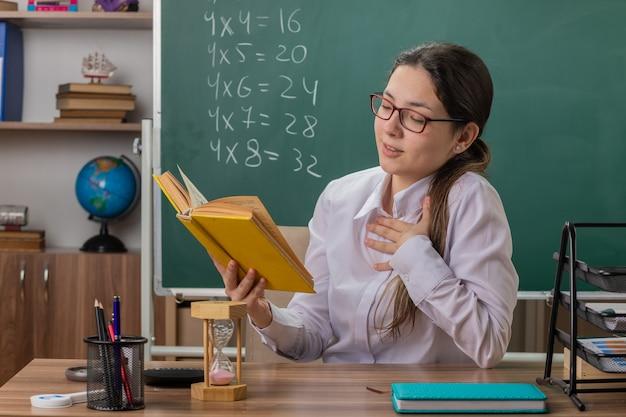 Professora jovem usando óculos segurando um livro se preparando para a aula de leitura, sentindo emoções positivas, sorrindo, sentada na mesa da escola em frente ao quadro-negro na sala de aula