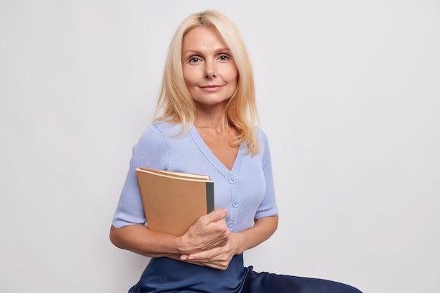 Professora loira bonita e séria se preparando para a aula segurando um caderno olhando diretamente para a frente posa bem vestida contra uma parede branca