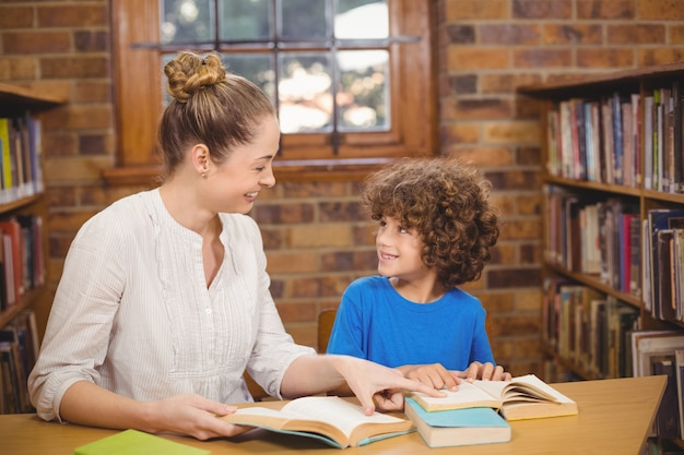 Professora loira e pupila lendo livros na biblioteca