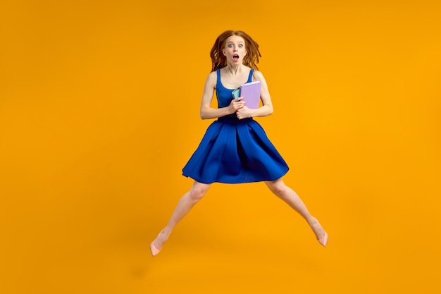 Professora louca e espantada com um vestido azul segurando livros nas mãos em estado de choque por alunos usando cabelos altos e rde está voando conceito de escola de educação de setembro