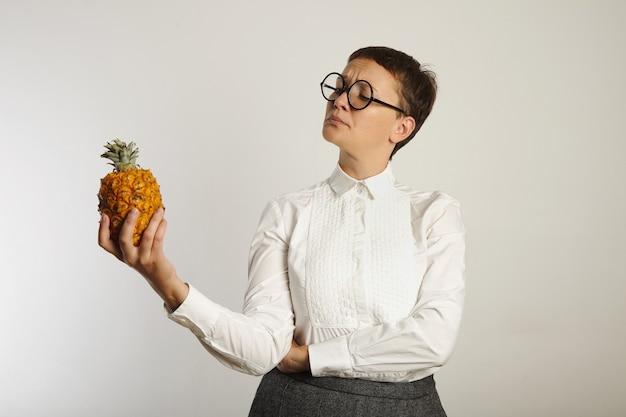 Professora maluca em roupa conservadora olhando interrogativamente para um abacaxi isolado no branco