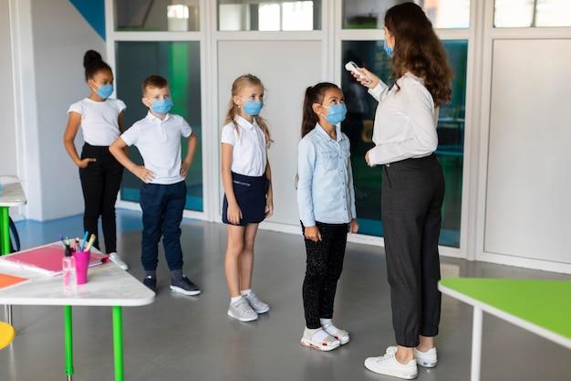 Professora medindo a temperatura de seus alunos