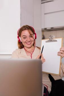 Professora mostrando aos alunos em aula online a lição no bloco de notas