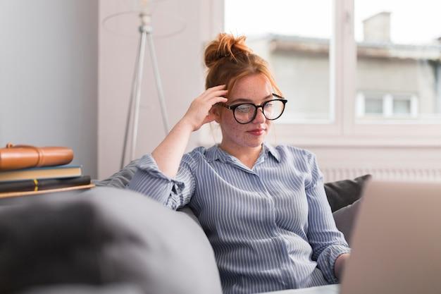 Professora no sofá em casa, dando uma aula online