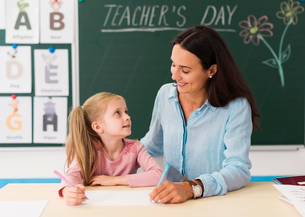 Professora olhando para sua pequena aluna