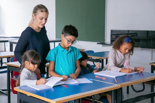 Professora positiva observando as crianças fazendo suas tarefas na sala de aula, sentadas em carteiras, desenhando e escrevendo em cadernos