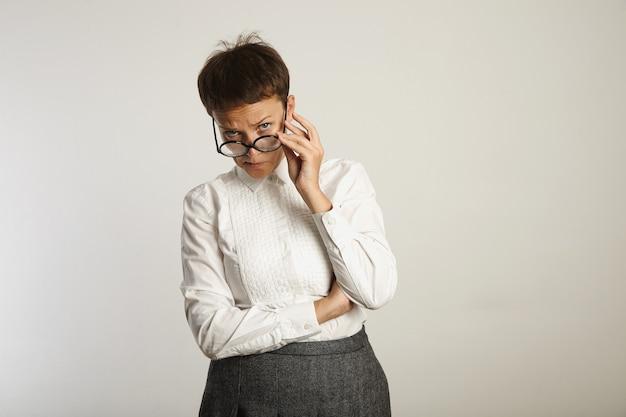Professora rígida parece desaprovadora e ajusta os óculos