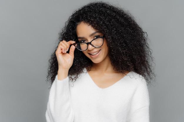Professora satisfeita mantém a mão na armação de óculos, sorri alegremente
