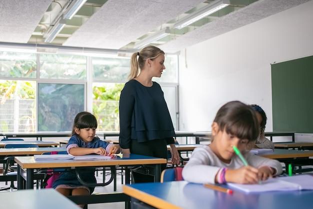 Professora séria observando crianças do ensino fundamental fazendo suas tarefas em sala de aula, sentadas em carteiras e escrevendo em cadernos