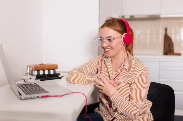 Professora sorridente com fones de ouvido, dando aulas on-line em casa