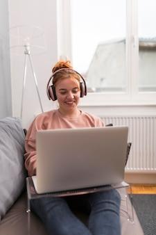 Professora sorridente com fones de ouvido no sofá, segurando uma aula online