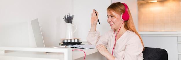 Professora sorridente com fones de ouvido, segurando uma aula online