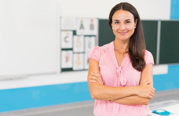Professora sorridente com os braços cruzados