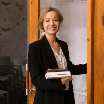 Professora sorridente com uma pilha de livros