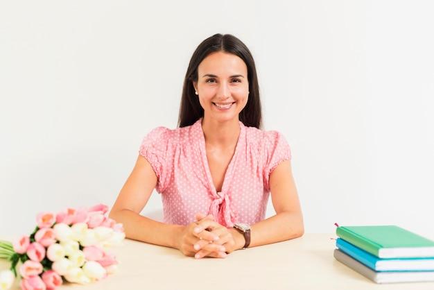 Professora sorridente de frente para a mesa posando em sua mesa