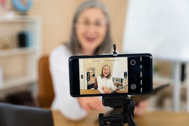 Professora sorridente de inglês fazendo aulas on-line em seu smartphone