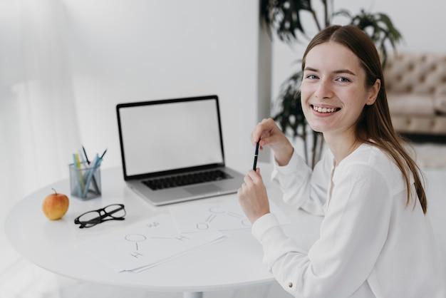 Professora sorridente em frente ao laptop