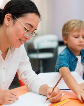 Professora sorridente fazendo aula com crianças