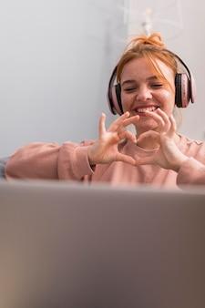 Professora sorridente mostrando sinal de coração para os alunos durante a aula online