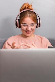 Professora sorridente usando laptop de casa para dar uma aula online
