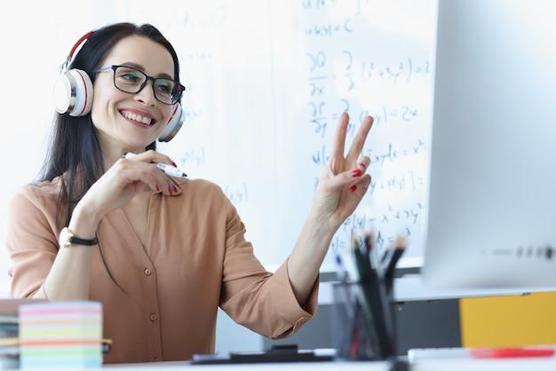 Professora usando fones de ouvido mostrando dois dedos na tela do computador