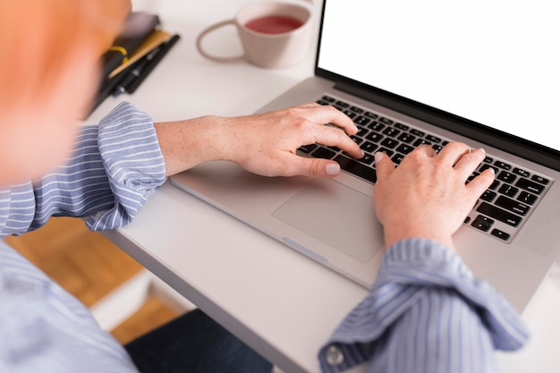 Professora usando laptop para escrever durante a aula online