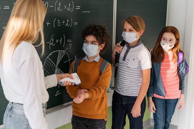 Professora verificando a temperatura das crianças na escola