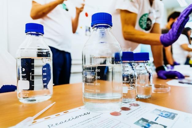 Professores de ciências em sala de aula mostrando experimentos para seus alunos em tubos de ensaio.