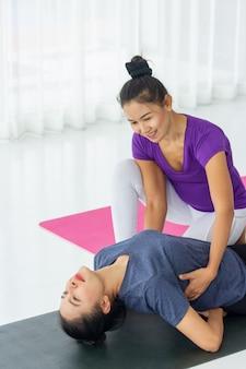 Professores de ioga asiáticos ensinam os alunos individualmente na academia a serem saudáveis e fortes.