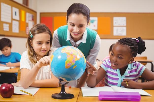 Professores e alunos olhando para o globo