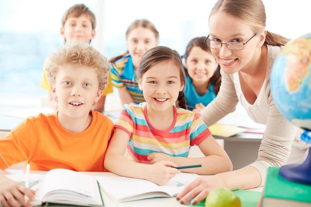 Professores e estudantes de sorriso na sala de aula