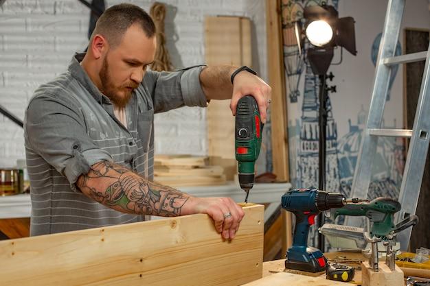 Profissão, carpintaria, marcenaria e conceito dos povos - carpinteiro com a furadeira elétrica que perfura a prancha de madeira na oficina