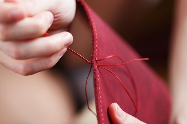 Profissão conceitual de um curtidor. as mãos da mulher se fecharam em torno da agulha e da linha.