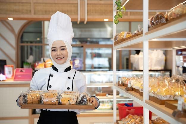 Profissão de chef atraente mulher muçulmana segurando bandeja sorrindo para a câmera usar hijab
