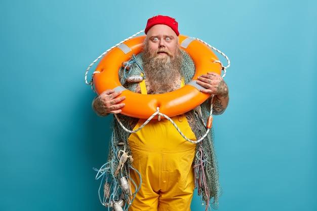 Profissão marinha. marinheiro barbudo e atordoado olha fixamente para os olhos esbugalhados, faz poses com uma argola de natação inflada e usa um macacão amarelo