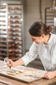 Profissão, pasteleiro. mulher experiente e alegre, confeiteira de uniforme branco, decorando éclairs com habilidade desenhando com fondant de chocolate
