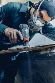 Profissão, pessoas, carpintaria, emoção e conceito de gente - um carpinteiro corta uma tábua com um quebra-cabeças elétrico. fabricação de skates. ele tem roupa de proteção e máscara. 4k