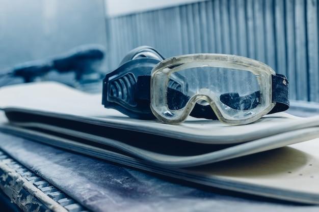Profissão, pessoas, carpintaria, emoção e conceito de gente - um carpinteiro corta uma tábua com um quebra-cabeças elétrico. fabricação de skates. ele tem roupa de proteção e máscara.