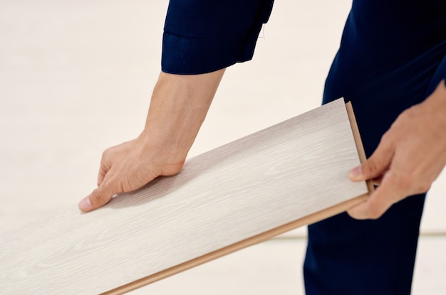 Profissionais da construção de pisos laminados para renovação de salas