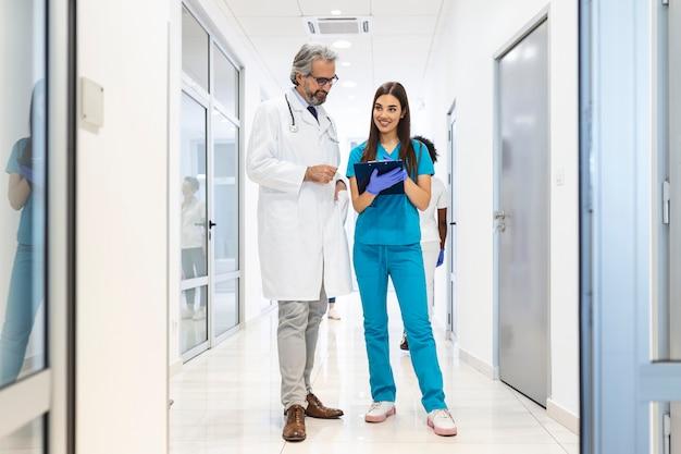 Profissionais de saúde em discussão no corredor do hospital.